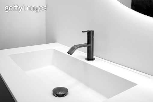 Bathroom interior with white sink and black modern techno style faucet
