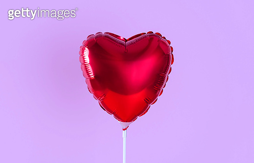 Red heart balloon isolated on lilac background. Creative minimal love concept.