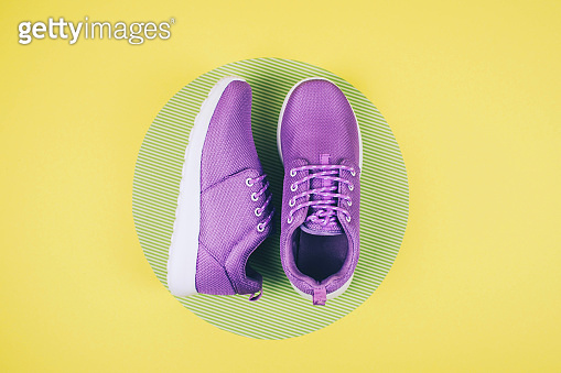 Lilac sneakers on a multi colored pastel surface