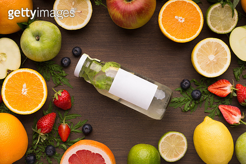 Bottle of detox water with fruits on wooden background