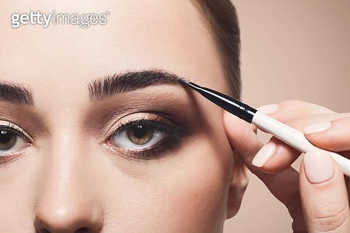 Make-up artist apply eyebrow shadow with brush, beauty