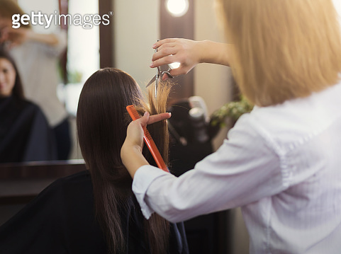 Hairdresser trimming long brown hair with scissors