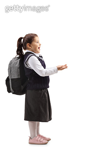 Surprised little girl in a school uniform holding her hands in front of her