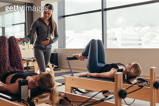 Pilates instructor training women at the gym