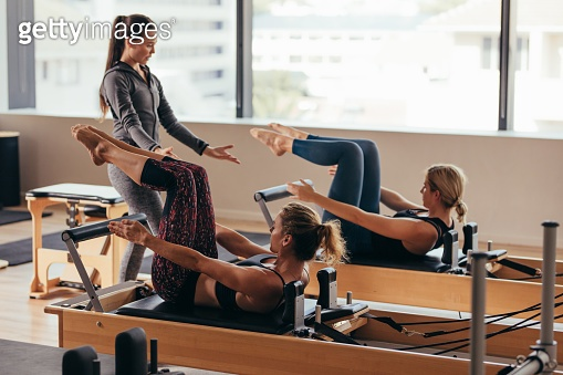 Pilates trainer instructing women at the gym
