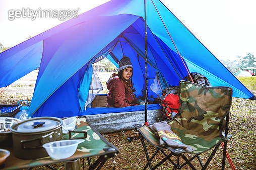 Asian women travel relax in the holiday. camping on the Mountain. sit and rest in the tent. Thailand