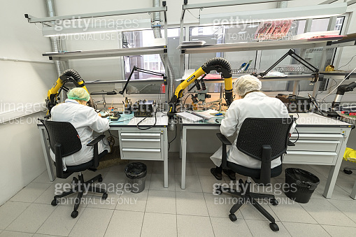 Women make soldering of radio components to electronic boards. Plant for the production of electronic equipment