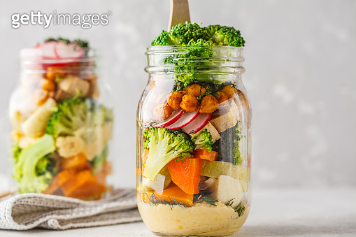Healthy Homemade Mason Jar Salad with baked vegetables, hummus, tofu and chickpeas.