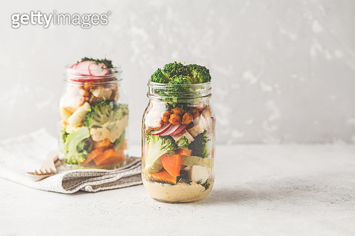 Healthy Homemade Mason Jar Salad with baked vegetables, hummus, tofu and chickpeas, copy space.