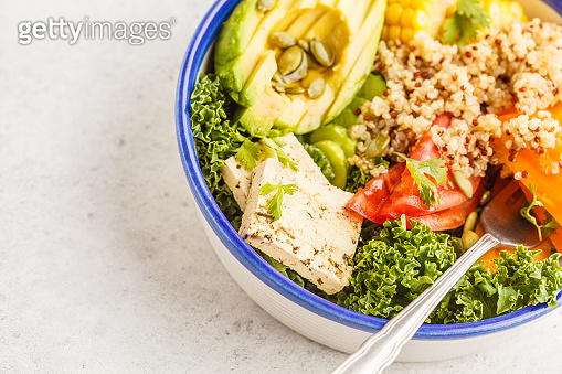 Vegan healthy rainbow salad, buddha bowl with quinoa, tofu, avocado and kale.