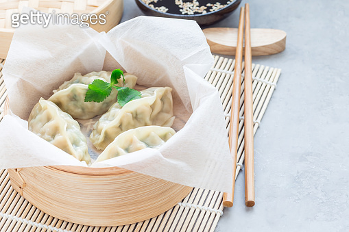 Steamed Korean dumplings Mandu with chicken meat and vegetables in bamboo steamer, horizontal, copy space