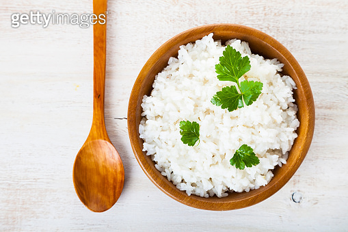 Boiled rice in a wooden bowl and spoon
