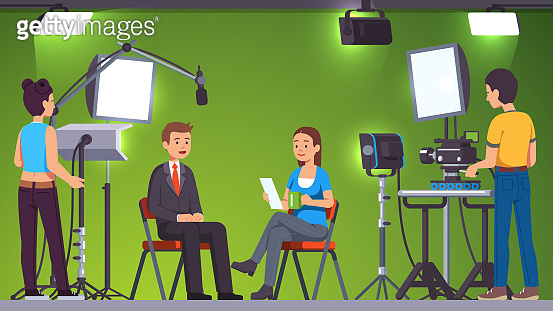 News television show live recording & broadcasting in professional video production studio set room with green background, lighting equipment, spotlights and cameras operated by cameramen shooting crew. TV host man talking to guest journalist woman taking