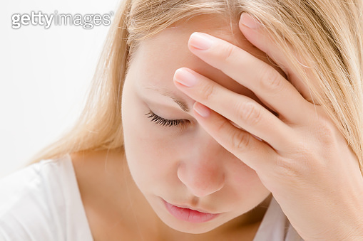 Young, adult blonde lady trying to calm down. Lonely, grieving, nervous woman touching head. Memory disorder. Suffering from burnout or other psychological problems. Women's issues. Face close up.