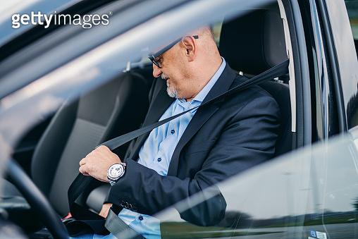 Bearded senior adult businessman fastening seat belt in his car.