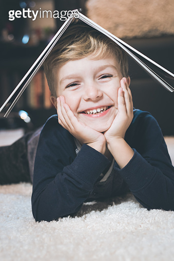 Portrait of happy kid with book on his head.