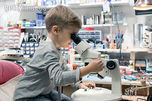 Little boy examining computer part while looking through the microscope.