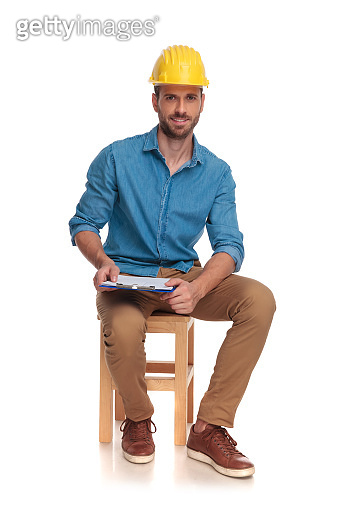 young seated construction engineer with clipboard