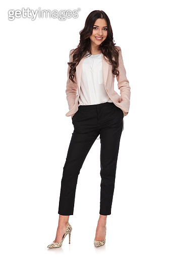 relaxed business woman standing with hands in her pockets