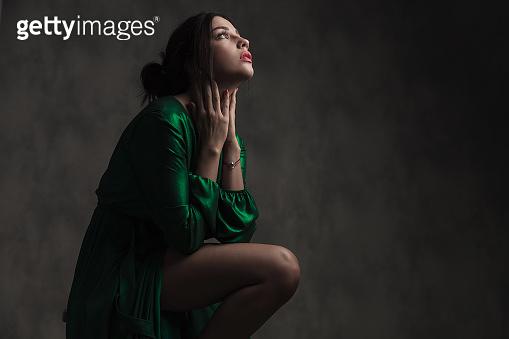sensual woman in green ballroom dress touching her neck