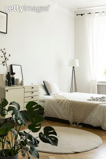 A monochromatic woman's bedroom interior with white and beige furniture, like a bed and a drawer cabinet. Copy space wall. Real photo.