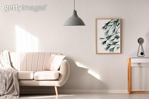Grey lamp in bright living room interior with poster next to beige sofa. Real photo