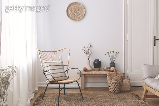 Armchair with pillow on brown rug in white natural living room interior with plants. Real photo