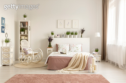 Rocking chair next to bed with blanket in spacious white bedroom interior with pink carpet. Real photo
