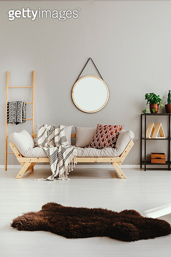 Brown fury rug on white floor of stylish ethno living room with scandinavian sofa with pillows and blanket, real photo with copy space on the empty beige wall