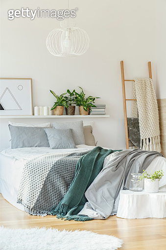 Bed in white bedroom interior