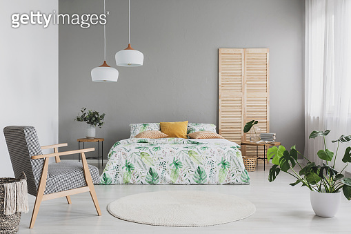 Armchair with houndstooth pattern placed in real photo of bright bedroom interior with two lamps, double bed with leafy sheets and cushions and Monstera Deliciosa plant standing on the floor