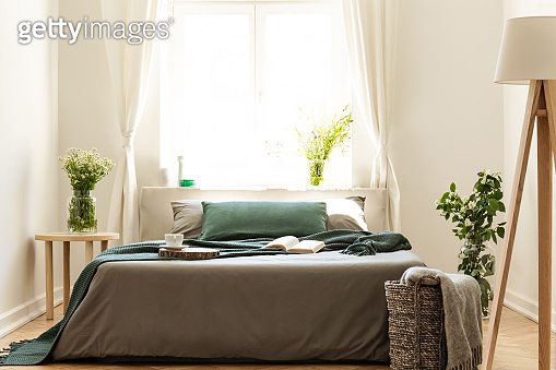 Eco friendly bedroom interior with a bed dressed in gray and green bedding. Sunny window as a background. Real photo.
