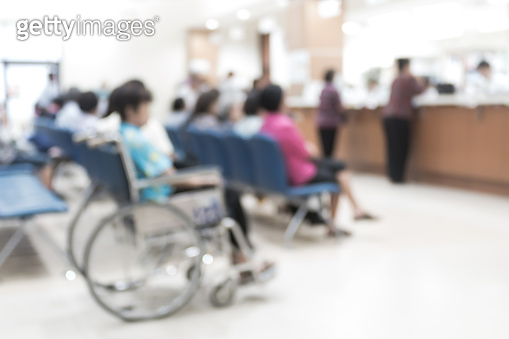 Blur medical background clinic service counter lobby with patient paying bill at cashier desk