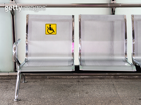 Stainless steel chairs in the train station with disabled signage to facilitate the use of train services for the disabled.
