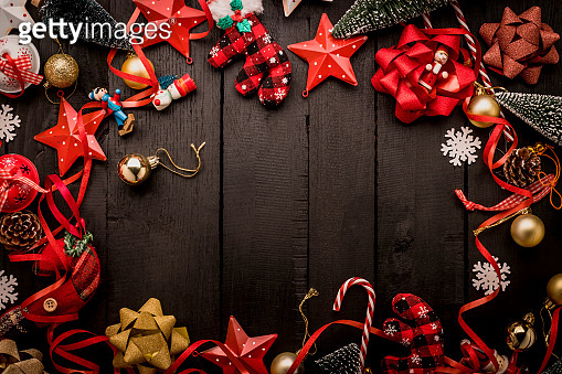 festive celebration background with christmas decorating items on black vintage wooden floor with free copy space