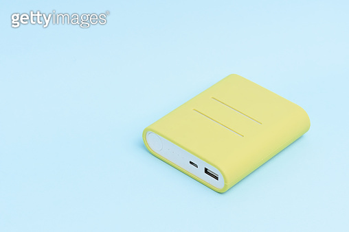 A yellow colored portable power bank isolated on light blue background.