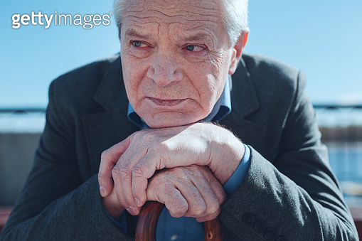 Senior man leaning on cane and thinking of old times