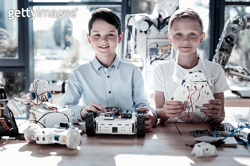 Joyful male friends constructing robotic machines