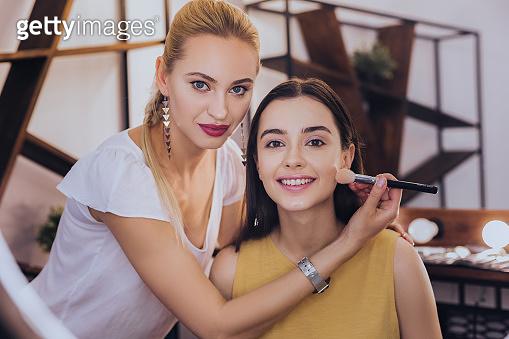 Dark-haired beaming woman enjoying talking to makeup artist