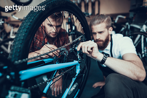 Guy and Bike Mechanic Repairs Bicycle in Workshop