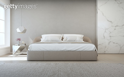 Bedroom of luxury house with double bed and carpet on wooden floor. Empty gray concrete wall background in vacation home or holiday villa.