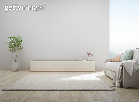 Sea view living room of luxury summer beach house with TV stand and wooden cabinet. Empty white concrete wall background in vacation home or holiday villa.