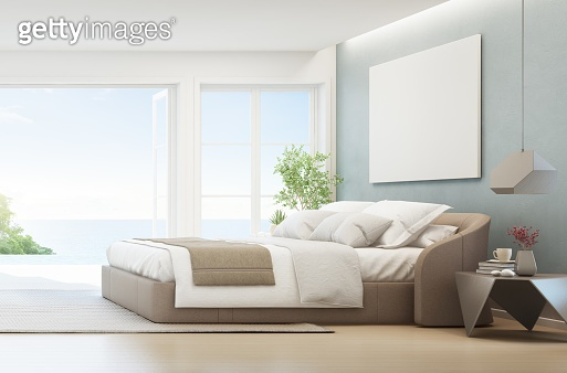 Sea view bedroom of luxury summer beach house with double bed near wooden floor terrace and swimming pool. Empty white frame on wall in vacation home or holiday villa.