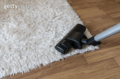 Cleaning white carpet, vacuum cleaner cleaning dust and dirtiness on carpet in living room