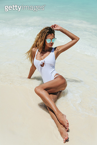 beautiful woman with blond hair and perfect slim body in luxurious swimming suit relaxing on Maldives