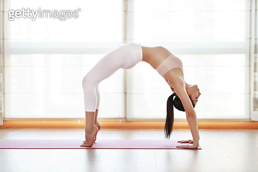 young woman practices yoga at  gym by window