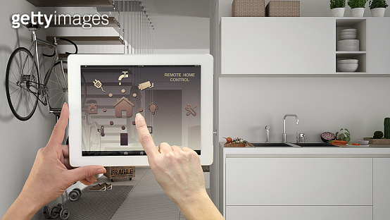 Smart remote home control system on a digital tablet. Device with app icons. Blurry interior of minimalist kitchen with stairs in the background, architecture design