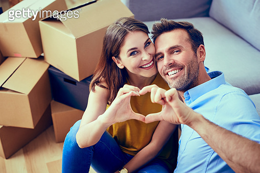 Happy couple during moving house showing heart sign
