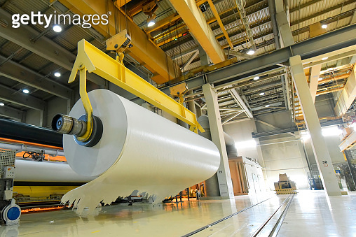 large roll of paper on a crane in a mill for the production of paper for further processing in a printing plant - recycling of waste paper