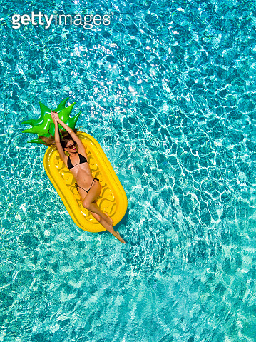Woman in bikini relaxes on a pineapple shaped float in a pool